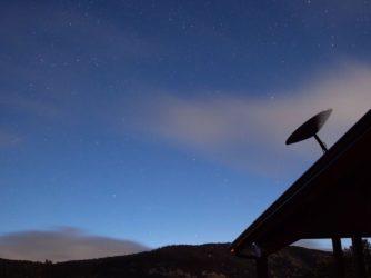 Anténa Starlink na střeše domu. V pozadí je noční obloha.